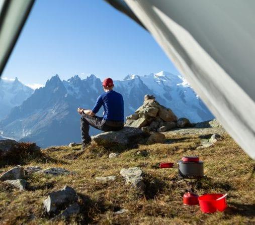 Un homme fait du bivouac en montagne