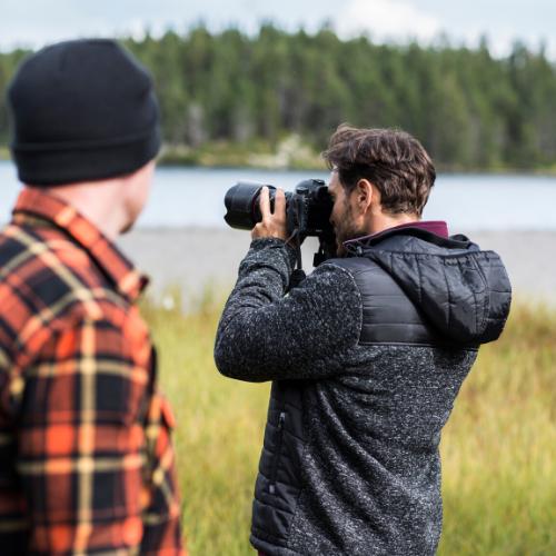 Un homme prend une photo d'un paysage en pleine nature