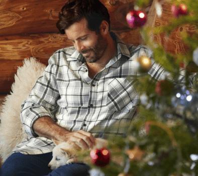Un homme est assis à coté d'un sapin de Noël